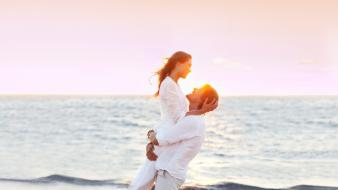Brunettes sunset ocean couple embrace bracelets white clothes wallpaper