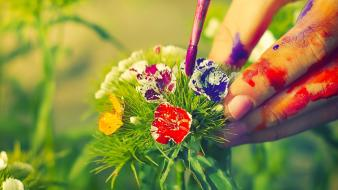 Multicolor flowers leaves hands paint brushes blurred background wallpaper