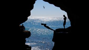 Birds silhouette rocks sunlight seagulls seascapes diving caves Wallpaper