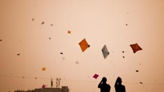 Silhouette people buildings kite festival pakistan roofs wallpaper