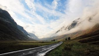 Mountains clouds wet valley asphalt way sky wallpaper