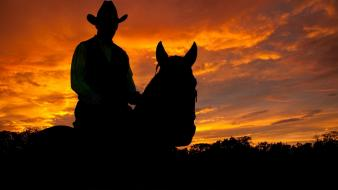 Cowboys horses men silhouettes sunset wallpaper